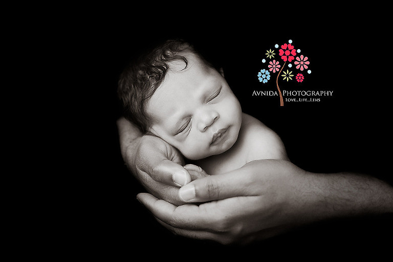 Picture of a cute newborn in daddys arms from your newborn photographer middletown nj