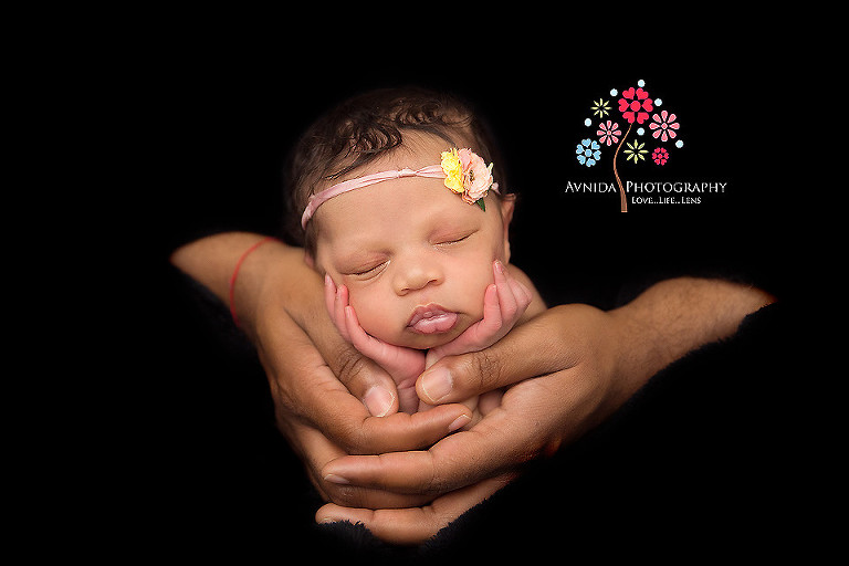 Picture of a cute newborn in daddys hands from your newborn photographer middletown nj