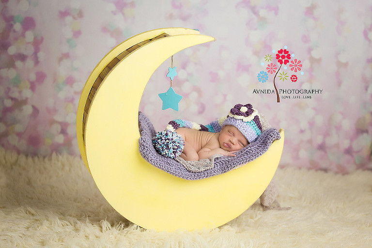 Picture of a cute newborn sleeping on a moon from your newborn photographer middletown nj by