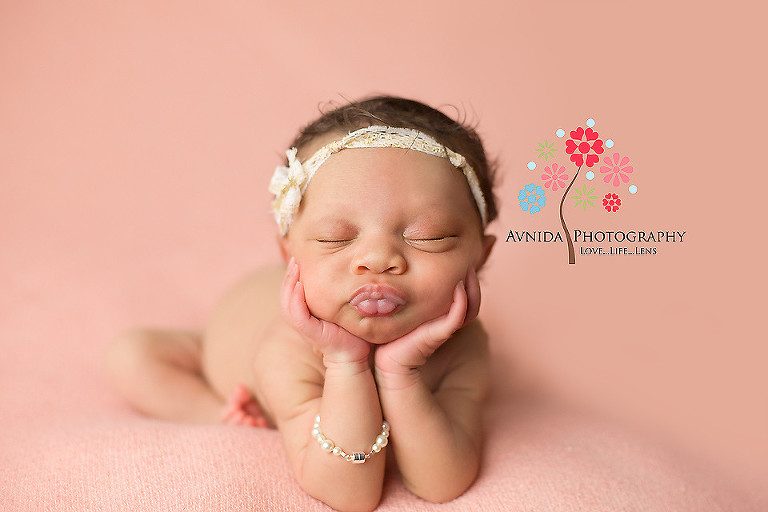Picture of a cute newborn with hands on her chin from your newborn photographer middletown nj