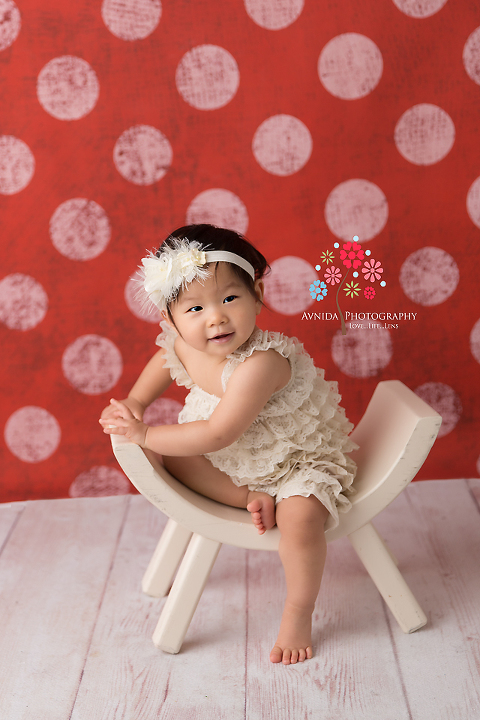 Cake Smash Photography Haworth NJ - A little tilt to the side, hint of a smile, a ruffled romper and cute little feet - we have the start of an awesome cake smash session