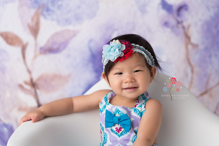 Cake Smash Photography Haworth NJ - This is what we do special, at Avnida Photography, for our little customers - Look at the flower on her headband and how it matches the colors on her dress.
