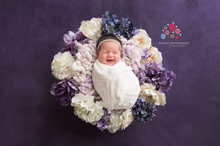 Newborn Photography Spring Lake NJ - This is probably one of the most favorite newborn photographs of all time - I love the colors, the dark lavender background, the flowers and most of all, the excited smile