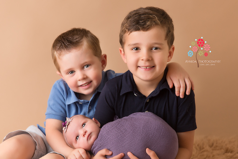 Newborn Photography Rumson NJ - Two cute, shiny eyed brothers completely in love with their cute baby sister, isn't this a wonderful sight