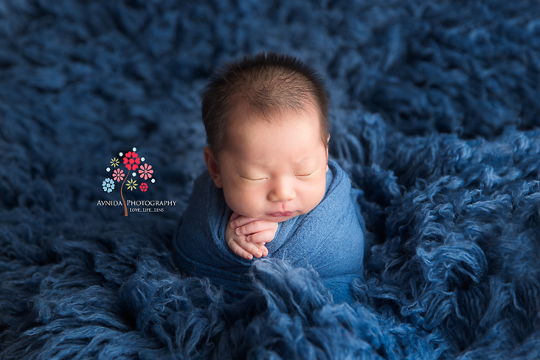 Newborn Photography Franklin Lakes NJ - The little yogi meditates in his deep thoughts, his arms crossed in a prayer while the sea of blue surrounds him