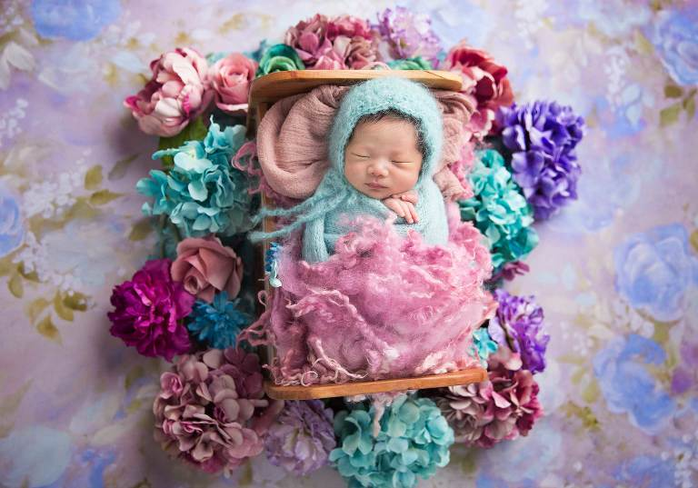 Sleeping newborn beauty enjoying her nap in bed of flowers